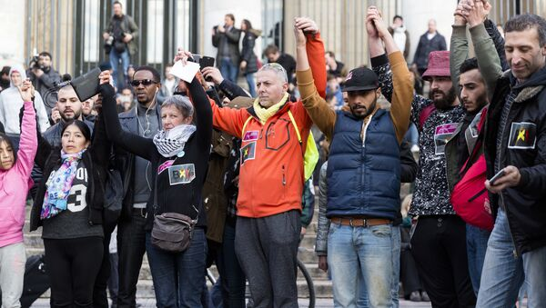 People stand hand in hand in tribute to victims at a makeshift memorial in front of the stock exchange at the Place de la Bourse (Beursplein) in Brussels on March 22, 2016 - Sputnik International