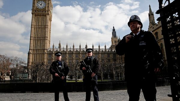 Armed British police officers stand on duty in front of the Elzabeth Tower, better known as Big Ben, outside the vehicle entrance to the Houses of Parliament in central London on March 22, 2016. - Sputnik International