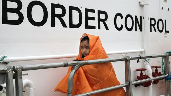 A refugee girl covered with a blanket and rescued at open sea prepares to disembark a Frontex patrol vessel at the port of Mytilene on the Lesbos island, Greece March 22, 2016. - Sputnik International