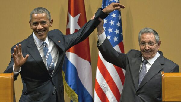 Cuban President Raul Castro, right, lifts up the arm of President Barack Obama at the conclusion of their joint news conference at the Palace of the Revolution, Monday, March 21, 2016, in Havana, Cuba - Sputnik International