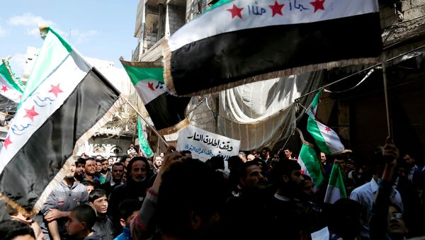 Syrian civilians and activists wave their national flags on the outskirts of the capital Damascus, on March 4, 2016. - Sputnik International