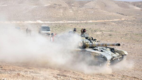 Forces loyal to Syria's President Bashar al-Assad drive a tank during their offensive to recapture the historic city of Palmyra in this picture provided by SANA on March 24, 2016. - Sputnik International