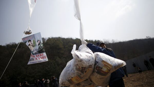 Park Sang-Hak, a North Korean defector living in the South and leader of an anti-North Korea civic group, holds a balloon containing leaflets denouncing North Korean leader Kim Jong Un, near the demilitarized zone separating the two Koreas in Paju, South Korea, March 26, 2016, on the sixth anniversary of the sinking of the naval ship Cheonan. - Sputnik International