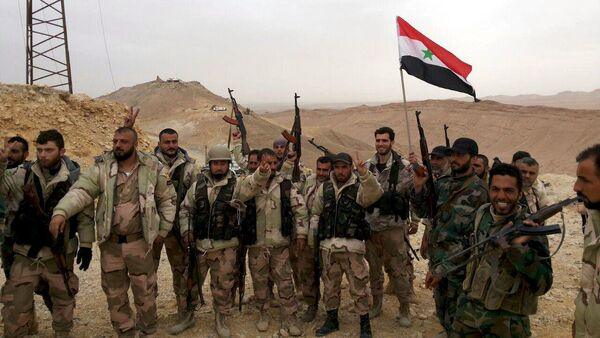 Forces loyal to Syria's President Bashar al-Assad flash victory signs and carry a Syrian national flag on the edge of the historic city of Palmyra in Homs Governorate, in this handout picture provided by SANA on March 26, 2016. - Sputnik International