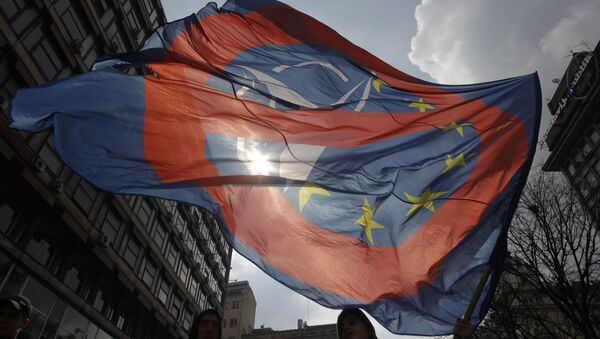 A man waves an anti NATO and EU flag during an anti NATO rally in downtown Belgrade, Serbia, March 27, 2016. - Sputnik International