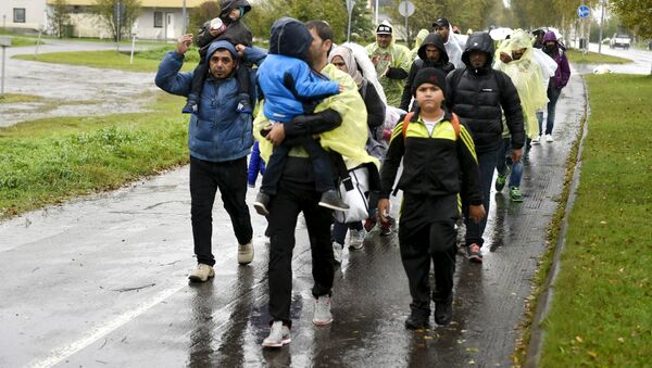 Refugees walk through the pouring rain from a public transport centre to the Lappia-building refugee reception centre in Tornio, northwestern Finland, on September 2015. - Sputnik International