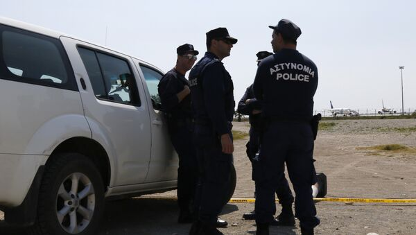Cypriot policemen stand guard in the vicinity of Larnaca airport where an EgyptAir Airbus A-320 (R) sits on the tarmac after being hijacked and diverted to Cyprus on March 29, 2016 - Sputnik International
