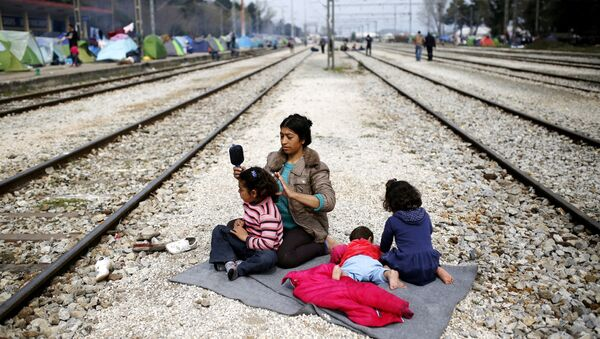 A woman sits with her children along railway tracks at a makeshift camp for migrants and refugees at the Greek-Macedonian border near the village of Idomeni, Greece, March 29, 2016. - Sputnik International