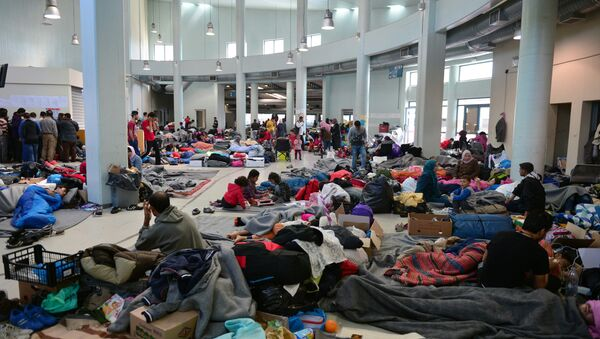 Migrants and refugees rest at the passengers terminal at the port of Piraeus where more than 5,500 migrants and refugees have found temporary shelter on March 30, 2016 - Sputnik International