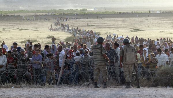 Turkish soldiers stand guard as Syrians wait behind the border fences near the southeastern town of Suruc in Sanliurfa province, Turkey (File) - Sputnik International