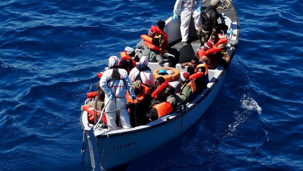 Migrants sit on a rescue boat during a rescue operation of migrants by Italian Navy vessels in this March 18, 2016 handout picture. - Sputnik International