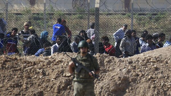 File photo of a Turkish army soldier guards the border area with Syria as in the background Syrian refugees wait in Syria in order to cross into Turkey, in Akcakale, southeastern Turkey, Monday, June 15, 2015 - Sputnik International