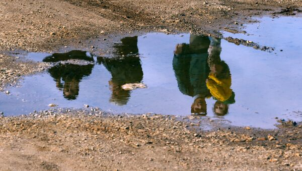 Syrian refugees are reflected in a puddle as they wait on a roadside after Turkish police prevented them from sailing off to the Greek island of Farmakonisi by dinghies, near a beach in the western Turkish coastal town of Didim, Turkey March 9, 2016. - Sputnik International