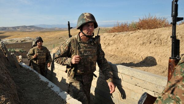 Armenian soldiers of the self-proclaimed republic of Nagorno-Karabakh walking in trenches at the frontline on the border with Azerbaijan. - Sputnik International
