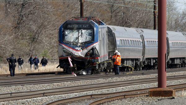 Emergency personnel examine the scene after an Amtrak passenger train struck a backhoe, killing two people, in Chester, Pennsylvania - Sputnik International