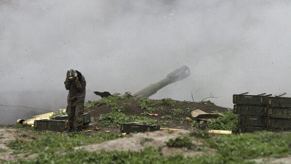 An Armenian serviceman of the self-defense army of Nagorno-Karabakh launch artillery toward Azeri forces in the town of Martakert in Nagorno-Karabakh region - Sputnik International