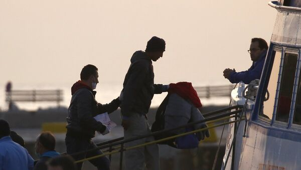A Frontex officer (L) escorts a migrant as he boards on a Turkish-flagged passenger boat to be returned to Turkey, on the Greek island of Lesbos, April 4, 2016. - Sputnik International
