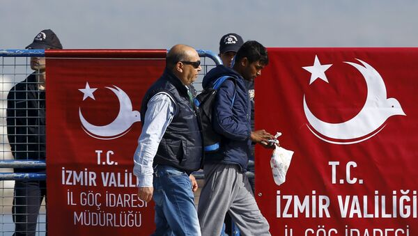 A migrant is escorted by a Turkish police officer as he arrives in the Turkish coastal town of Dikili, Turkey, April 4, 2016 - Sputnik International