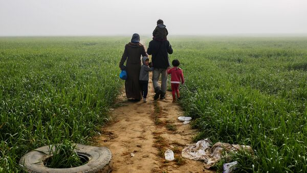 A family walks through a field at a makeshift camp for migrants and refugees at the Greek-Macedonian border near the village of Idomeni, Greece, April 4, 2016. - Sputnik International