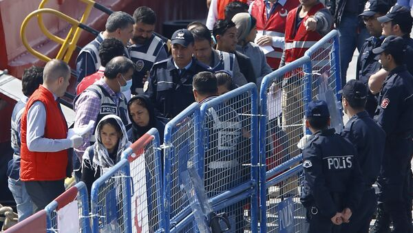 Migrants are escorted by Turkish police officers as they arrive in the Turkish coastal town of Dikili, Turkey, April 4, 2016. - Sputnik International