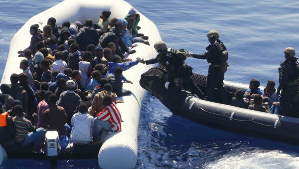 German Navy sailors surround a boat with more than 100 migrants near the German combat supply ship 'Frankfurt am Main' during EUNAVFOR Med, also known as Operation Sophia, in the Mediterranean Sea off the coast of Libya, Tuesday, March 29, 2016 - Sputnik International