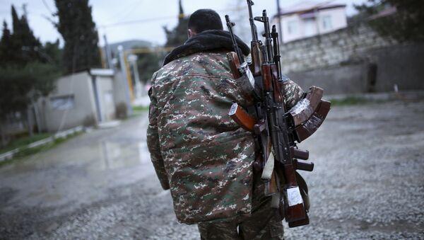 An ethnic Armenian fighter carries Kalashnikov machine guns to his comrade-in-arms at Martakert province in the separatist region of Nagorno-Karabakh, Azerbaijan, Monday, April 4, 2016 - Sputnik International