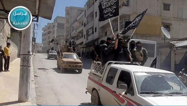 This image posted on the Twitter page of Syria's al-Qaida-linked Nusra Front on Saturday April 25, 2015, which is consistent with AP reporting, shows Nusra Front fighters standing on their vehicles and waving their group's flags as they tour the streets of Jisr al-Shughour, Idlib province, Syria - Sputnik International