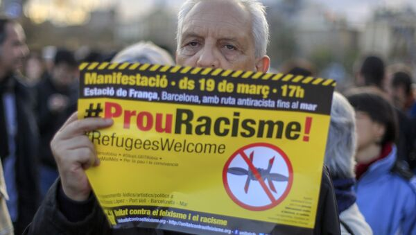 """A protester called by Stop Mare Mortum and """"Unity against Fascism and Racism"""" platforms, holds a poster reading Stop Racism in Catalan during the European March for Refugee Rights in Barcelona on March 19, 2016. - Sputnik International"""
