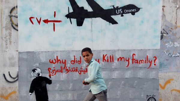 A Yemeni boy (C) walks past a mural depicting a US drone and reading  Why did you kill my family on December 13, 2013 in the capital Sanaa. - Sputnik International