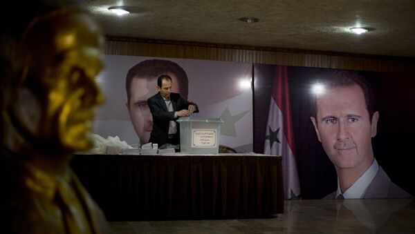 A Syrian election official waits for voters at a polling station with posters of President Bashar Assad during the parliamentary election in Damascus, Syria - Sputnik International