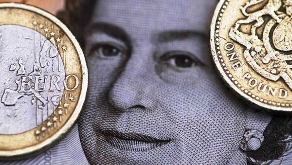 A two Euro coin is pictured next to a one Pound coin on top of a portrait of Britain's Queen Elizabeth in this file photo illustration shot March 16, 2016. - Sputnik International
