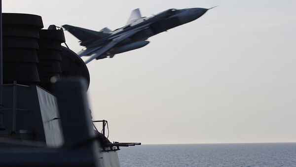 An undated US Navy picture shows what appears to be a Russian Sukhoi SU-24 attack aircraft making a very low pass close to the U.S. guided missile destroyer USS Donald Cook in the Baltic Sea. - Sputnik International
