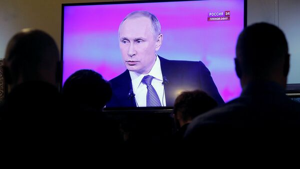 Journalists watch a live broadcast on an electronic screen showing nationwide call-in attended by Russian President Vladimir Putin in Moscow, Russia, April 14, 2016 - Sputnik International