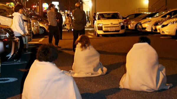 People wrapped in blankets sit on the road as they are evacuated from a hotel after an earthquake in Kumamoto, southern Japan, in this photo taken by Kyodo April 14, 2016 - Sputnik International