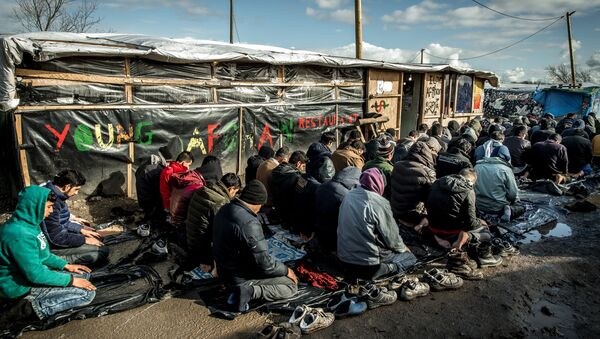 Men pray  in the migrants and refugee camp in Calais, northern France. File photo - Sputnik International