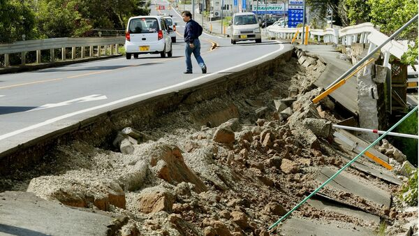 A man walks near a damaged road caused by an earthquake in Mashiki town, Kumamoto prefecture, southern Japan, in this photo taken by Kyodo April 15, 2016 - Sputnik International