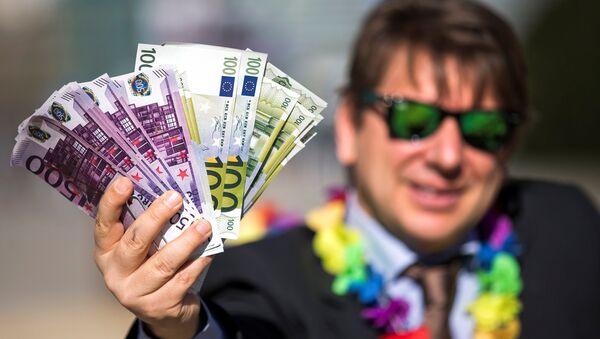 An activist shows fake banknotes during a demonstration outside the European Commission (EC) - Sputnik International