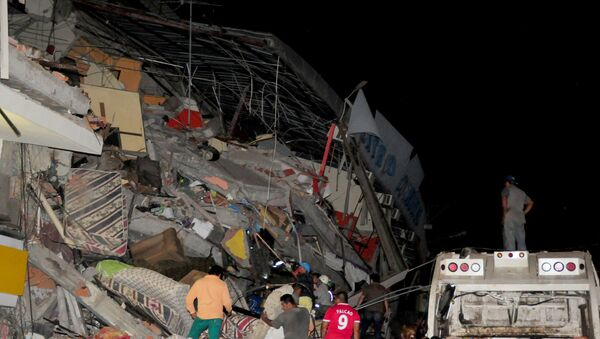 People stand next to the debris of a building after an earthquake struck off the Pacific coast, in Manta, Ecuador, April 16, 2016 - Sputnik International