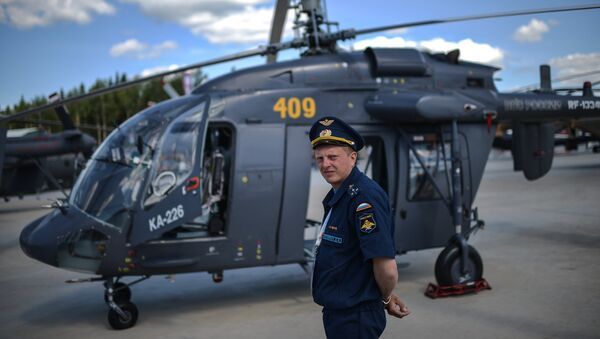 A pilot stands next to a Ka-226 helicopter at the ARMY-2015 international military technical forum held outside Moscow. - Sputnik International