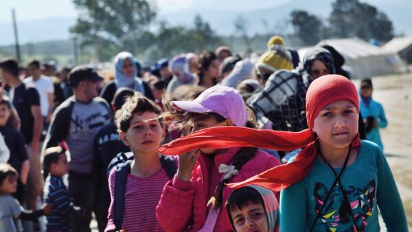 Refugees and migrants queue for food at the makeshift camp along the Greek-Macedonian border near the village of Idomeni on April 20, 2016. - Sputnik International