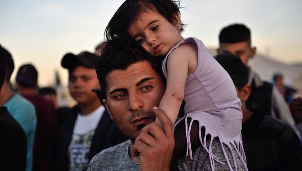 A man carries a child on his shoulders at the migrant and refugee makeshift camp near the village of Idomeni on the Greek-Macedonian border on April 16, 2016. - Sputnik International