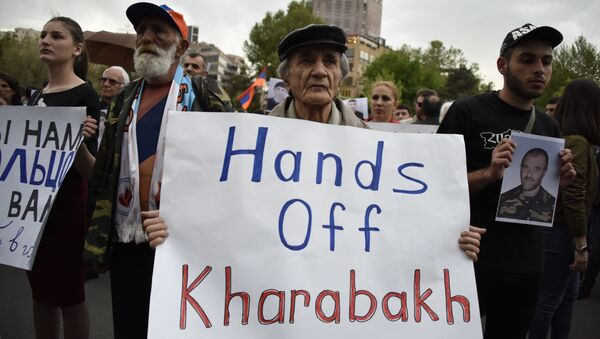 An Armenian man holds a placard reading Hands off Karabakh as he takes part in a rally in Yerevan on April 21, 2016. - Sputnik International