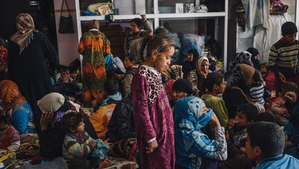 Child stands among women and children in a building housing displaced civilians, in Makhmour, east of Mosul, Iraq (File) - Sputnik International