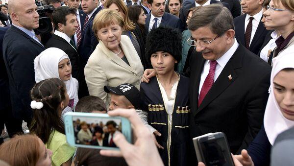 Turkish Prime Minister Ahmet Davutoglu and German Chancellor Angela Merkel pose for a picture with refugees in Nizip refugee camp near Gaziantep, Turkey, April 23, 2016 - Sputnik International