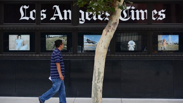 A pedestrian walks past a display of photographs at the Los Angeles Times Building in downtown Los Angeles, California on July 10, 2013 - Sputnik International