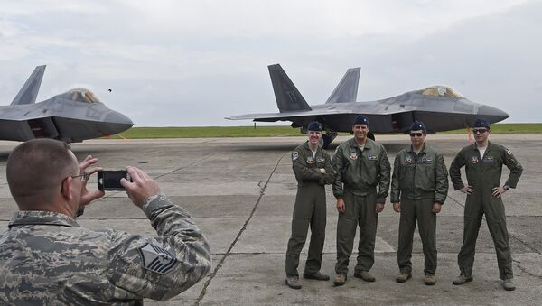 US pilots pose for a photograph in front of US F-22 Raptor fighters parked on the runway at Mihail Kogalniceanu air base in Romania April 25, 2016. - Sputnik International