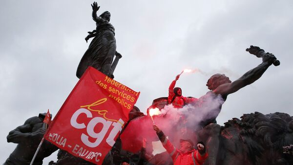French CGT labour union workers hold safety flares as they stand on the statue of the Place de la Nation during a demonstration against the French labour law proposal in Paris. - Sputnik International