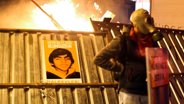 A protester stands in front of a barricade bearing a portrait of Berkin Elvan, the 15-year-old boy who died from injuries suffered during last year's anti-government protests, following clashes between police and demonstrators after the funeral of Elvan, in Istanbul on March 12, 2014. - Sputnik International
