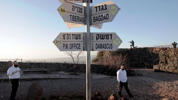 Israelis walk near a sign for tourists showing the distance to Damascus and Baghdad among other destinations at an army post on Mount Bental in the Israeli-annexed Golan Heights on March 10, 2016. - Sputnik International