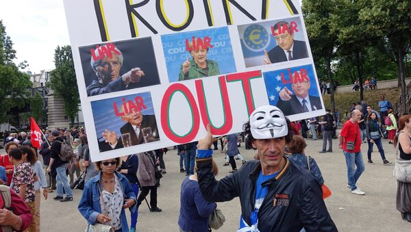 A man holds a sign that reads Troika Out as people take part in a demonstration called by associations, unions and left-wing politicians in support of both migrants and the Greek people on June 20, 2015 in Paris. - Sputnik International
